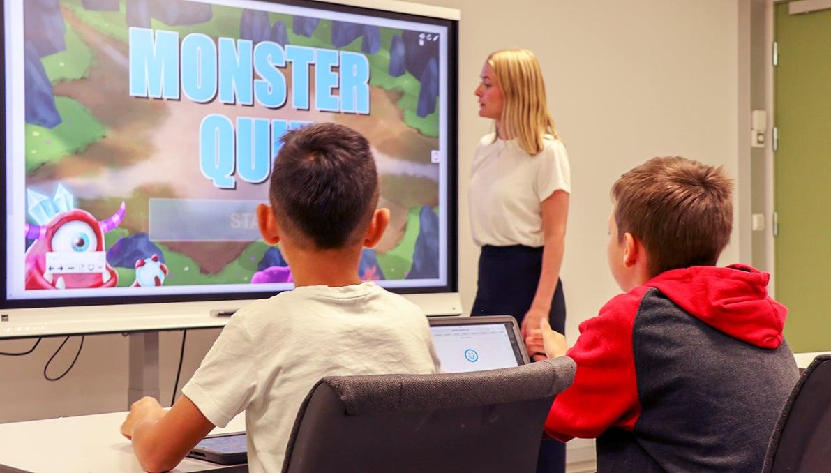 Lærer og elever med interaktiv skjerm i undervisningen.